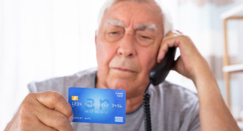 Un homme au cheveux gris parle au téléphone avec sa carte de crédit à la main.