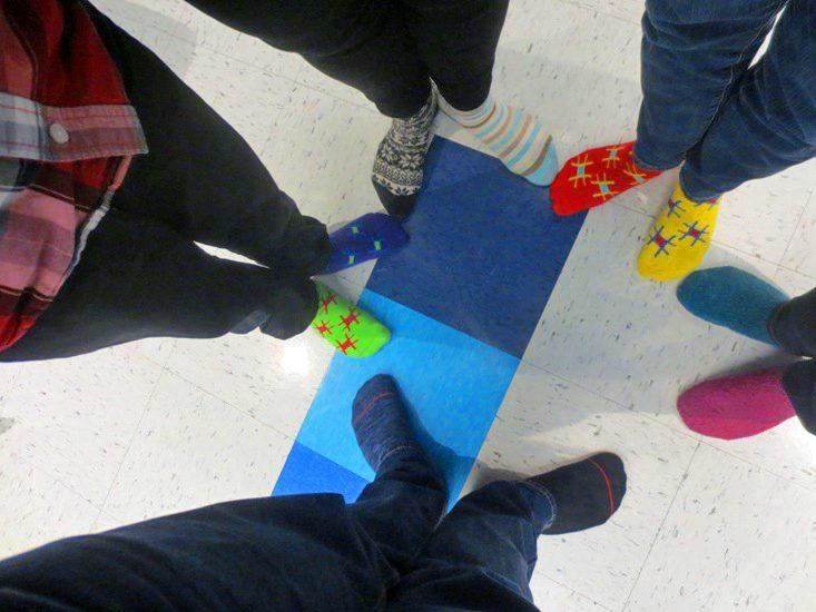 La photo montre les pieds de cinq personnes qui portent tous des bas de couleurs différente.