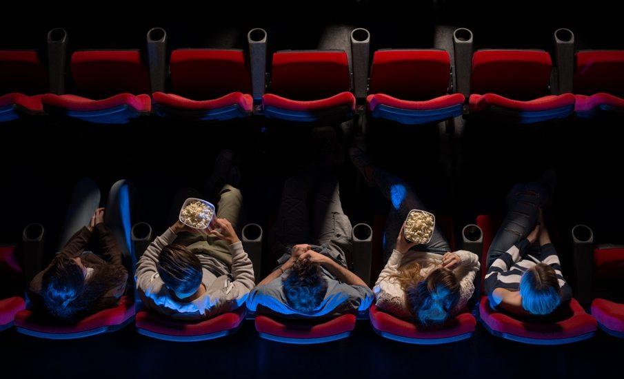 vu de haut, des personnes assises sur des sièges de cinéma mangent du pop corn.