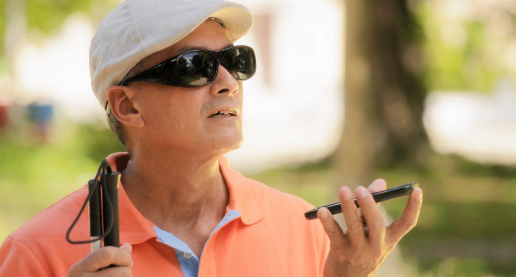 Homme aveugle avec téléphone et canne