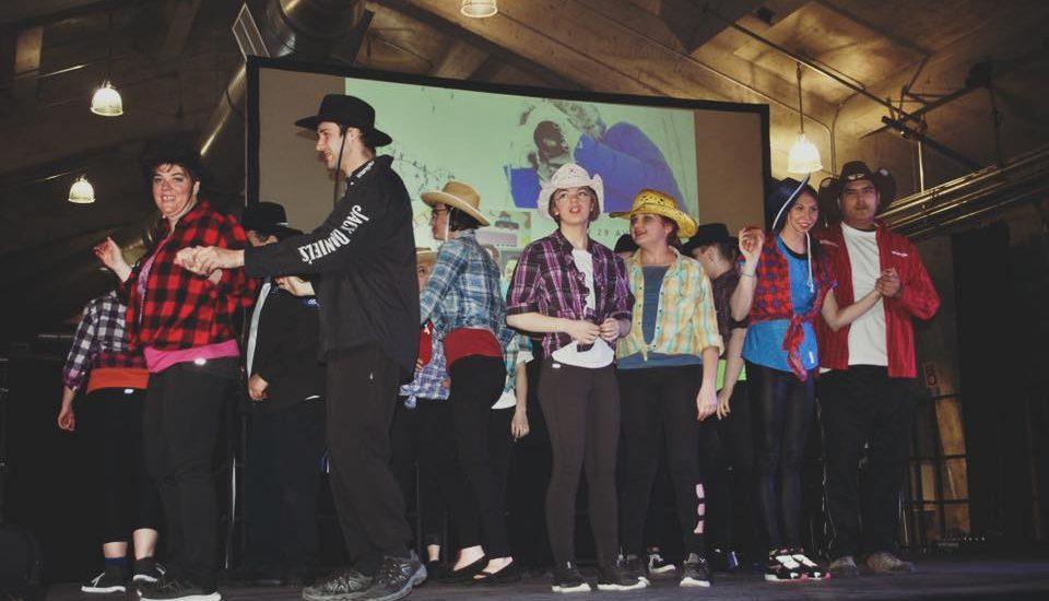 Des participants du festival son sur une scène et portent tous des chapeaux de cowboy.