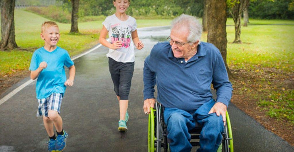 Un homme aux cheveux gris est assis sur un fauteuil roulant vert. Deux enfants courent à côté de lui.