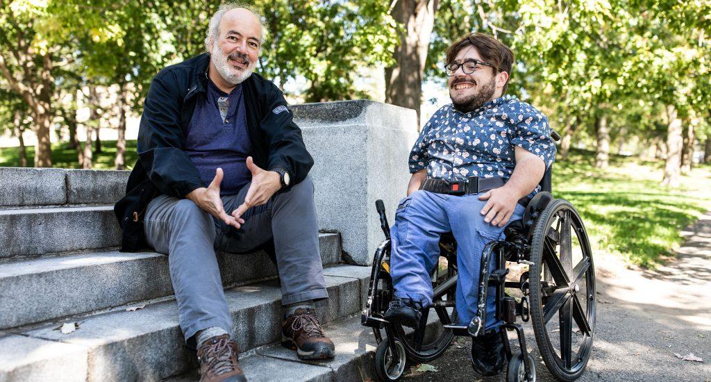 François Bodeur et Kéven Breton sont photographiés dans un parc, en été. François Brodeur est assis sur des marches en ciment. Kéven Breton est en fauteuil roulant.