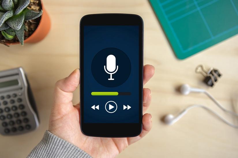 Au-dessus d'une table une main caucasienne tiens un téléphone intelligent. Tout prêt sur la table, on voit des écouteurs. Sur le téléphone, on voit un dessin de microphone, symbole usuel de la balladodiffusion.