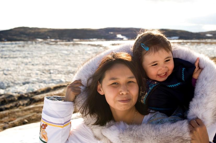 Une femme autochtone avec un enfant sur ses épaules, à l'extérieur