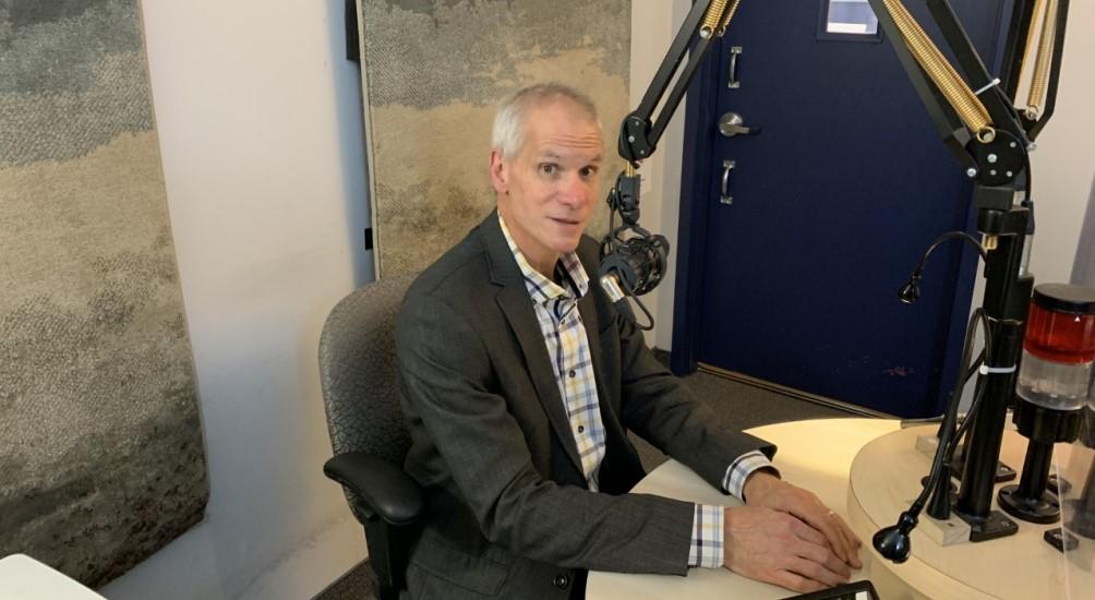François Beauregard, un homme au cheveux gris courts, est assis devant le micro dans le studio de Canal M.
