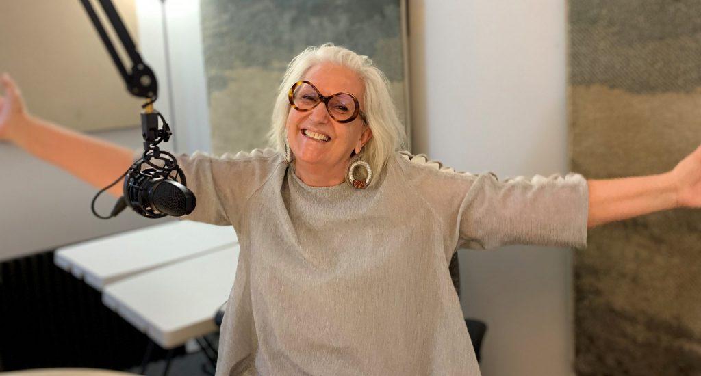 Arlette Fara, en studio, souriante les bras ouverts