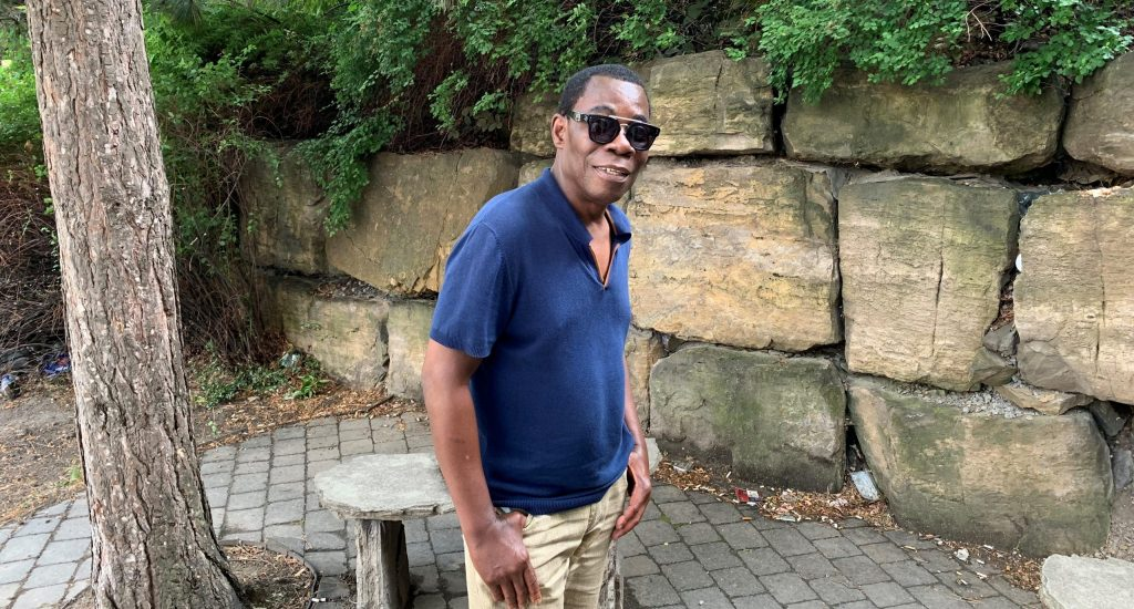 Fulgence Bla, devant un mur de pierre, avec un chandail bleu et des lunettes fumées