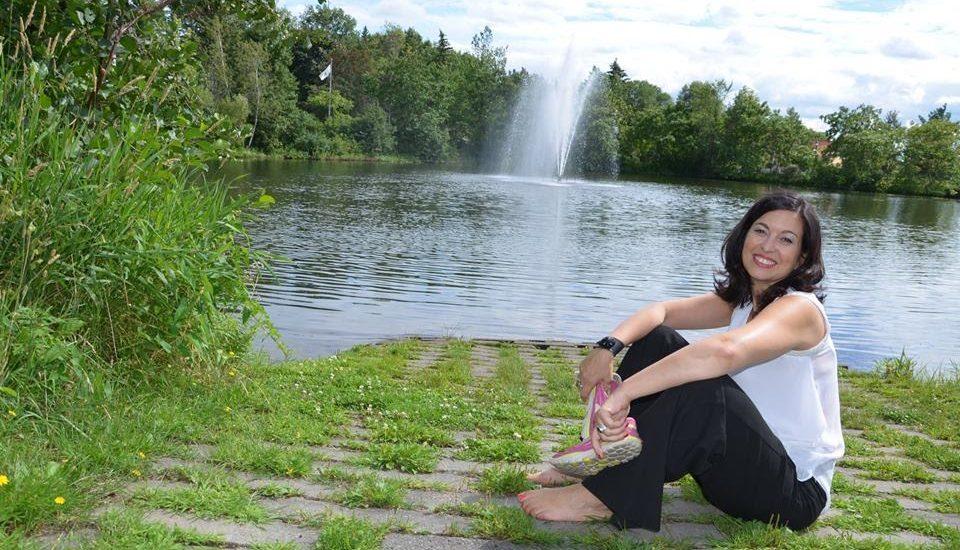 Chantal Dauray, assise devant une étendu d'eau, avec au loin une fontaine