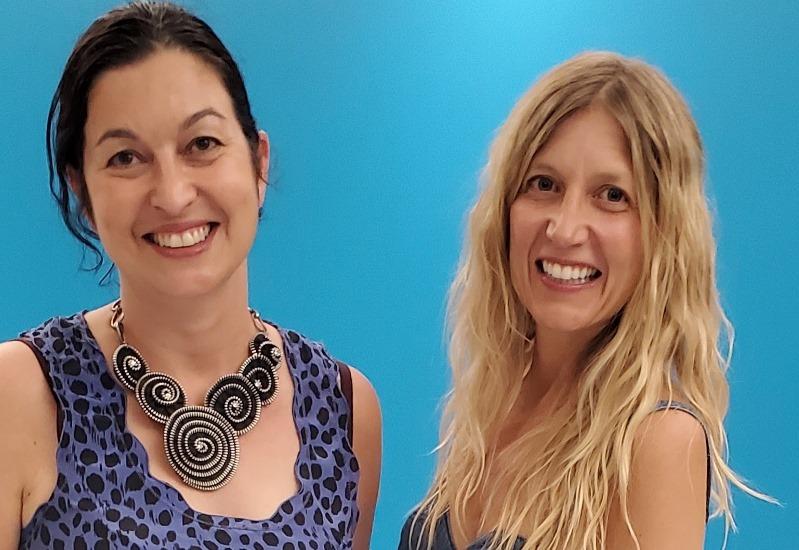 À gauche, Chantal Dauray, une femme aux cheveux bruns foncés et attachés, elle porte une robe bleue et un collier noir. À droite, Marie-Ève Fortier, une femme aux cheveux blonds et ondulés.