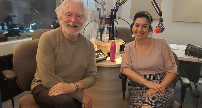Dans un studio de radio, on voit à gauche un homme caucasien aux cheveux et à la barbe blanche, qui porte des lunettes. À droite, une femme caucasienne aux cheveux noirs attachés. Les deux sont souriants.